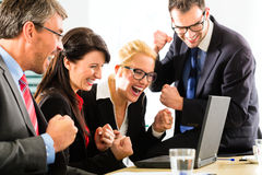 Business people looking at laptop with success Stock Photos