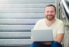 Business and freedom. Happy modern businessman, man with a beard behind a laptop in nature sits smiling on the steps and running. Stock Photos