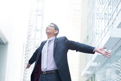 Business freedom. Indian businessman open his arms wide, looking up into the light, modern office building as background, natural sunlight Stock Photos