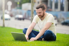 Business and freedom. Modern business man with a beard behind a laptop outdoors on grass. Stock Photo