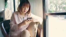Business freelance Asian woman using smartphone for talking, reading and texting while sitting on table in cafe. stock footage