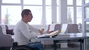 Business freelance, successful ailing male on wheel chair uses modern computer technology for remote work to development stock video footage