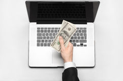 Business and freelance topic: hand in a black suit holding money dollars on a laptop on a white background table studio isolated t Royalty Free Stock Photography