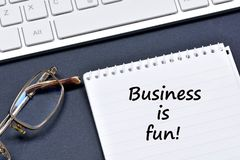 Business is fun text on notebook. On a black background Stock Image