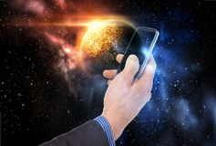 Hand holding smartphone over planet in space. Business, future technology and people concept - businessman hand holding smartphone over planet in space Stock Images