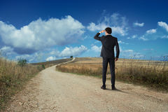 Business future view. Businessman looks at the horizon from a rural road Royalty Free Stock Photo