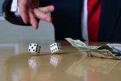 Business is a gamble series #3. Closeup of businessmans hand tossing two white dice Stock Image