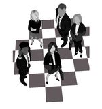 Business Game. Business people standing on a chessboard Stock Photography