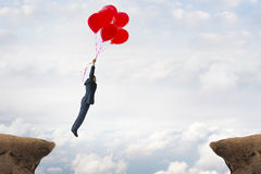 Business gap concept. Businessman flying over a crevasse using helium balloons Stock Photo