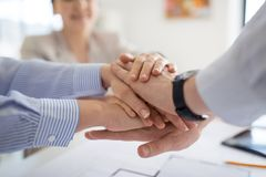 Close up of business team stacking hands stock photo