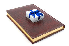 Business gift on leather datebook. Small gift box laying on the leather notebook, isolated on white Royalty Free Stock Image