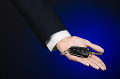 Business and gift theme: car salesman in a black suit holds the keys to a new car on a dark blue background in studio Stock Photography
