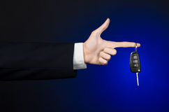 Business and gift theme: car salesman in a black suit holds the keys to a new car on a dark blue background in studio Royalty Free Stock Photography