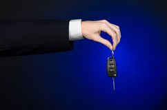Business and gift theme: car salesman in a black suit holds the keys to a new car on a dark blue background in studio Stock Image