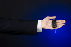 Business and gift theme: car salesman in a black suit holds the keys to a new car on a dark blue background in studio Stock Photos