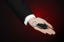 Business and gift theme: car salesman in a black suit holds the keys to a new car on a dark red background in studio Royalty Free Stock Photo