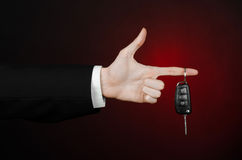 Business and gift theme: car salesman in a black suit holds the keys to a new car on a dark red background in studio Royalty Free Stock Photography