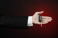 Business and gift theme: car salesman in a black suit holds the keys to a new car on a dark red background in studio Stock Photo