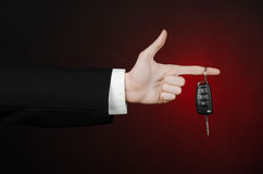 Business and gift theme: car salesman in a black suit holds the keys to a new car on a dark red background in studio. Business and gift theme: car salesman in a Stock Images