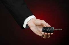 Business and gift theme: car salesman in a black suit holds the keys to a new car on a dark red background in studio. Business and gift theme: car salesman in a Royalty Free Stock Photo