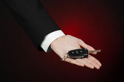 Business and gift theme: car salesman in a black suit holds the keys to a new car on a dark red background in studio Stock Image