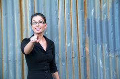 Business Girl. Young, empowered business woman pointing at the camera and smiling Stock Image