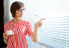 Business Girl. A woman holding a coffee in the window Stock Image