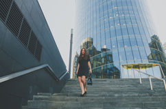 Business girl in a dress walks down the stairs holding a bag Royalty Free Stock Photography