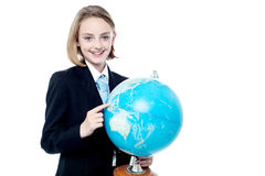 Business girl indicating a place in globe map Royalty Free Stock Photography