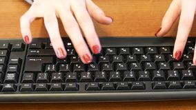 Business girl with a nice manicure typing on black keyboard. Close-up of woman hands typing on pc keyboard stock video
