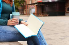 A girl with notebook. Business girl with a notebook and a cup of hot coffee Royalty Free Stock Images