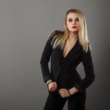 Business girl posing in the studio. On a gray background stock photography