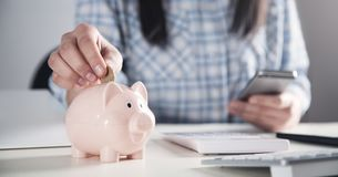 Free Business Girl Putting Coin In A Piggy Bank. Saving Money Royalty Free Stock Photography - 145860817