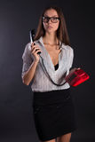 Business girl. Secretary girl in glasses on a black background with telephone Stock Photo