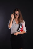 Business girl. Secretary girl in glasses on a black background wiyh folder and smile Royalty Free Stock Image