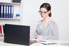 Business girl sits at a computer in the Office paper folders Stock Photo