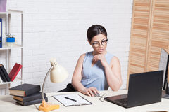 Business girl sits in an Office behind a desk with a computer royalty free stock image