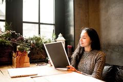Business girl studying the menu in restaurant decorated with Christmas decor.sits near the window on cloudy winter day at wooden t Royalty Free Stock Images