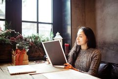 Business girl studying the menu in restaurant decorated with Christmas decor.sits near the window on cloudy winter day at wooden t Royalty Free Stock Photography