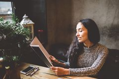 Business girl studying the menu in restaurant decorated with Christmas decor.sits near the window on cloudy winter day at wooden t Stock Photo