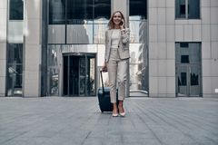 Business on the go. Full length of young woman in suit pulling luggage and smiling while walking outdoors royalty free stock photography