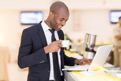 Business on the go. Cheerful young African man in formalwear using his laptop while standing at the bar Royalty Free Stock Photos