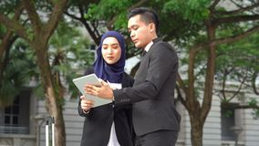 Business on the go concept. Muslim business people discussing while checking on tablet pc, outdoor business stock video