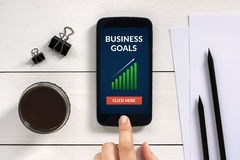 Business goals concept on smart phone screen with office objects Stock Photos