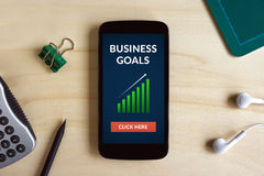 Business goals concept on smart phone screen on wooden desk Royalty Free Stock Photo