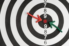 Business goals or financial target, green and red arrow pointing at red dot center of black and white circle dartboard with score stock photo