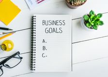 Business goals with notepad on office desk table with supplies Stock Image