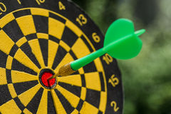 Business goals or targets concept with selective focus on a dart. Pin in the center of dartboard with green bokeh background Royalty Free Stock Images