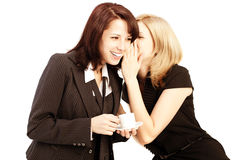 Business gossip. Women in the office. Two girls discuss the news. At lunchtime with coffee. Gossip, rumors, secrets and intrigue royalty free stock photos
