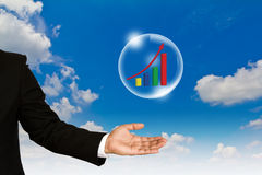 Business graph in bubble over business man hand ag Stock Photography